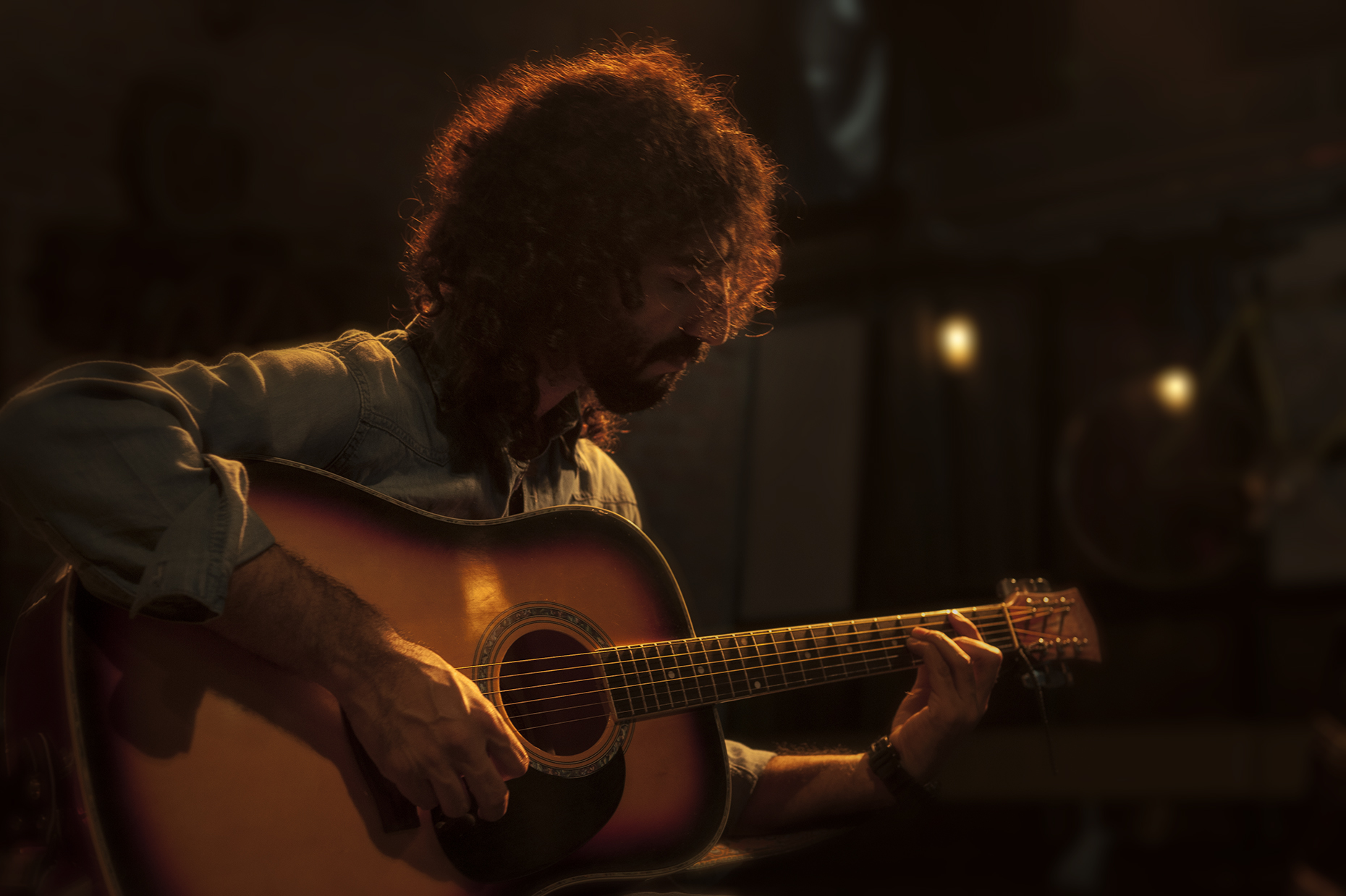 Portrait of a curly haired man playing guitar.